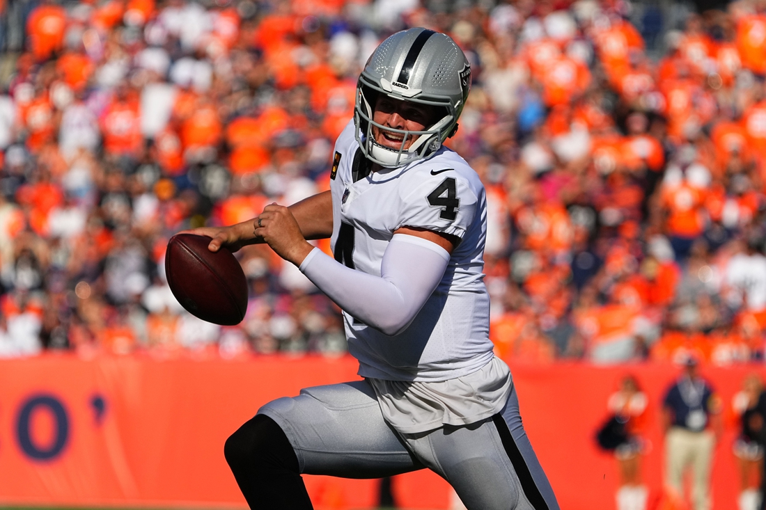 Oct 17, 2021; Denver, Colorado, USA; Las Vegas Raiders quarterback Derek Carr (4) scrambles with the ball in the first half against the Denver Broncos at Empower Field at Mile High. Mandatory Credit: Ron Chenoy-USA TODAY Sports