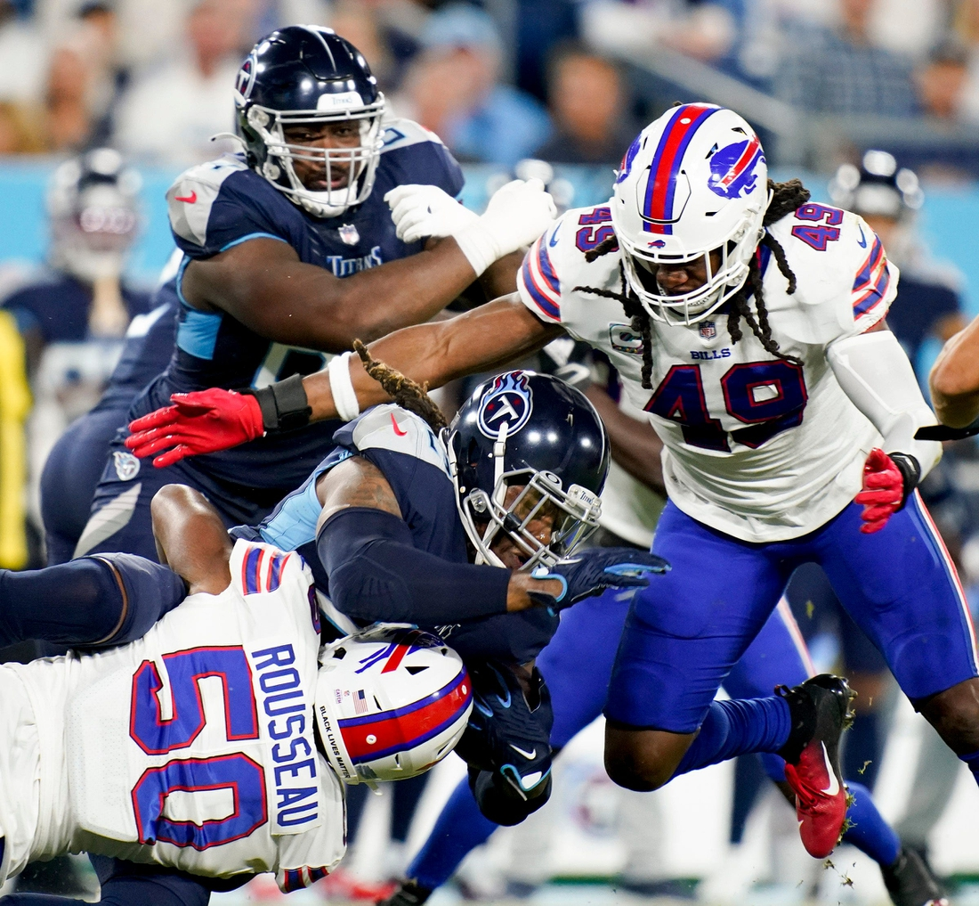 Tennessee Titans running back Derrick Henry (22) is tackled by Buffalo Bills defensive end Greg Rousseau (50) and middle linebacker Tremaine Edmunds (49) at Nissan Stadium Monday, Oct. 18, 2021 in Nashville, Tenn.