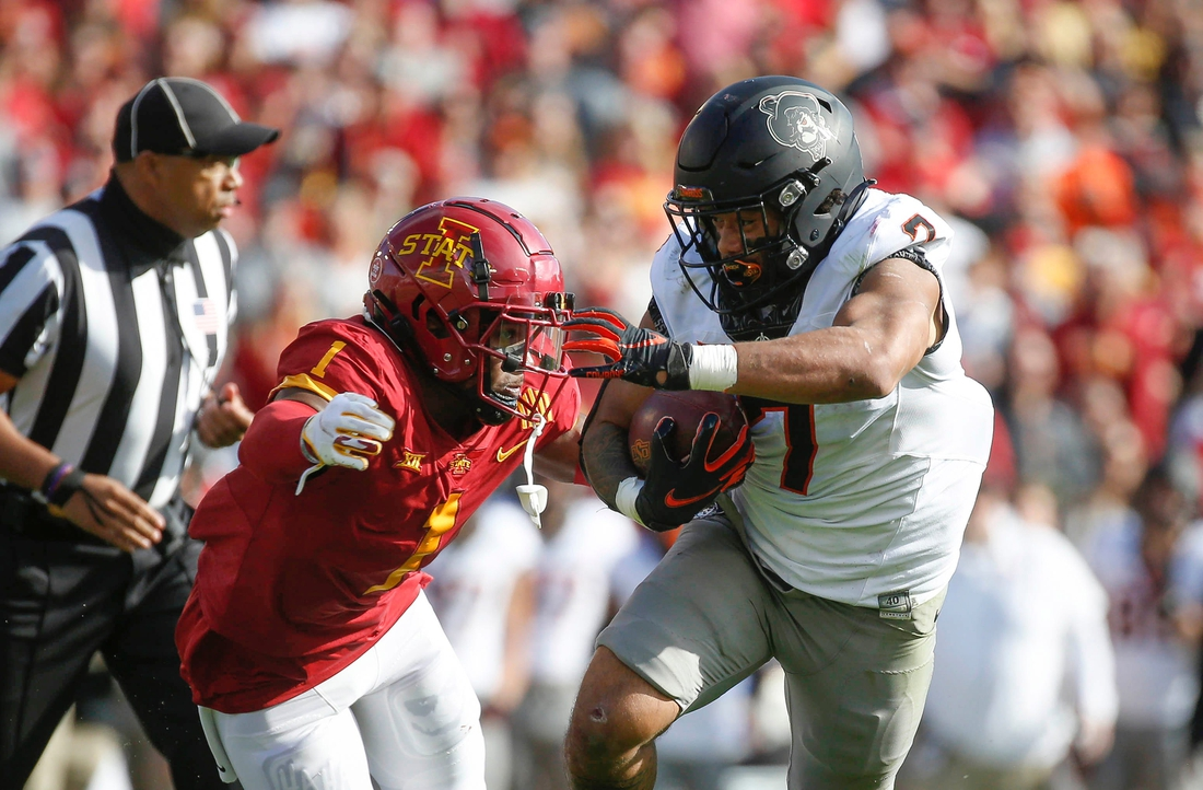 Oklahoma State senior running back Jaylen Warren runs the ball as Iowa State sophomore defensive back Isheem Young applies defense in the first quarter on Saturday, Oct. 23, 2021, at Jack Trice Stadium in Ames.  20211023 Iowastatevsokst