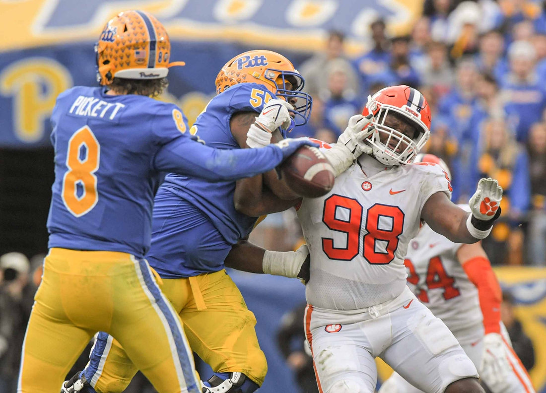 Pitt quarterback Kenny Pickett (8) throws near  Clemson defensive end Myles Murphy (98) trying to get by Pitt offensive lineman Marcus Minor (55)  during the second quarter at Heinz Field in Pittsburgh, Pennsylvania, Saturday, October 23, 2021.  Ncaa Football Clemson At Pitt