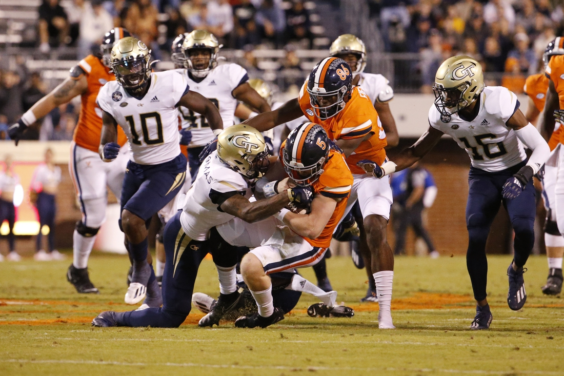 Oct 23, 2021; Charlottesville, Virginia, USA; Virginia Cavaliers quarterback Brennan Armstrong (5) carries the ball as Georgia Tech Yellow Jackets defensive back Juanyeh Thomas (1) tackles during the first quarter at Scott Stadium. Mandatory Credit: Amber Searls-USA TODAY Sports